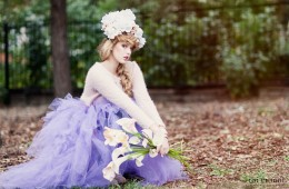 Portrait in the park of a beautiful girl with flowers and a purple tulle skirt