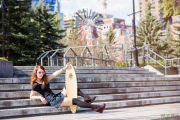 Posing with Arbor longboard for a fashion portrait in historic Eau Claire in Calgary.