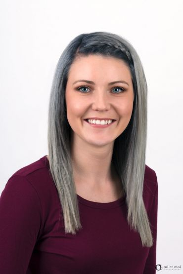 Smiling, friendly, approachable headshot of a young female professional in Calgary